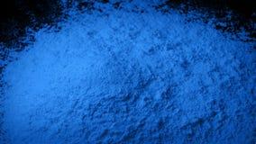 Blått pulver hälls in i högen stock video