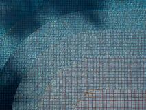 Blått rev sönder vatten i simbassäng med mosaiken för den keramiska tegelplattan för trappan i bakgrund Arkivbild