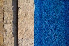 Blått rivit sönder vatten i simbassäng i tropisk semesterort med kanten av trottoar Del av simbassängbottenbakgrund royaltyfria bilder