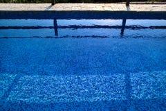 Blått rivit sönder vatten i simbassäng i tropisk semesterort med kanten av trottoar Del av simbassängbottenbakgrund royaltyfria foton