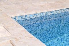 Blått rivit sönder vatten i simbassäng i tropisk semesterort med kanten av trottoar Del av simbassängbottenbakgrund arkivfoto