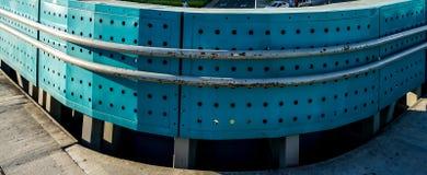 Blått runt staket med helheter som göras av metall Arkivfoto