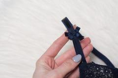 Blått snör åt behån i kvinnlig hand Modedamunderkläderbegrepp close upp arkivbild