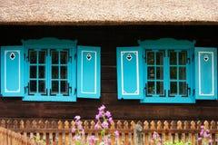 Blått stänger med fönsterluckor trähuset Arkivbild