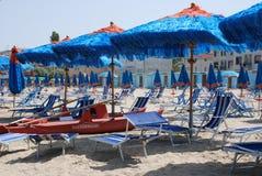 Blått strandparaplyer och livfartyg Arkivbild