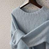 Blått stucken woolen tröja på en hängare Arkivfoto