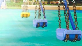 Blått svänger i en lekplats med en klartecken i parkera bifokal royaltyfri fotografi