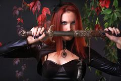 Blått synade den röda Head gotiska flickan som rymmer ett fantasisvärd bland höstvinrankor royaltyfri bild