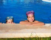Blått synar barn som flickor på på blått slår samman att le för poolside Royaltyfri Foto