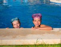 Blått synar barn som flickor på på blått slår samman att le för poolside Royaltyfri Bild