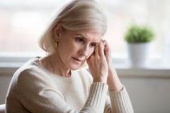 Blått tänka för fundersam ledsen mellersta åldrig kvinnakänsla av anxiet arkivbild
