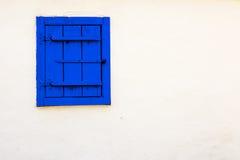Blått tappningfönster på den vita väggen Arkivfoto