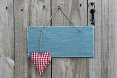 Blått tecken för antikvitet på den wood dörren med hjärta- och järntangenter Arkivfoto