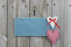 Blått tecken för antikvitet som hänger på den wood dörren med hjärtor och järntangent Arkivbild