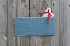 Blått tecken för antikvitet som hänger på den wood dörren med muslinhjärta Royaltyfri Bild