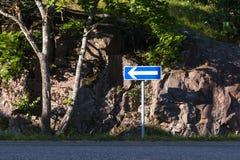 Blått tecken med den vänstra pilen på sidan av vägen Arkivfoton