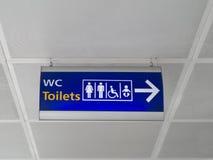 Blått tecken med en kontur av mannen, kvinnlign, rullstolen och barnet En pekare till läget av toaletten Royaltyfri Fotografi