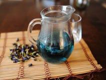 Blått thailändskt te som är anchan i genomskinlig glass tillbringare på bambu som är matt på trätabellen Placer av torkade blommo Royaltyfria Bilder