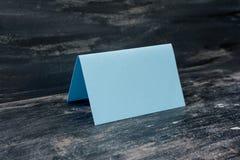 Blått tomt kort på tabellen Stranda av hår vänder mot in royaltyfria bilder