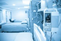 Blått tonar av sängar och bearbetar med maskin i sjukhus. Arkivfoton