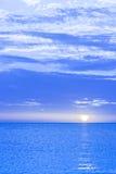 Blått tonat solnedgånghimmel och hav. Arkivfoton