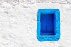 Blått träfönster på den vita stenväggen, Grekland Royaltyfri Bild