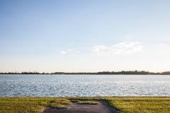 Blått vatten av Palic sjön, i Subotica, Serbien, med en grön gräsmatta i förgrunden, under en sommarsolnedgång arkivfoto