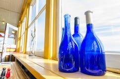 Blåttflaskor i ett fönster bredvid havet, Newfoundland Kanada royaltyfria bilder