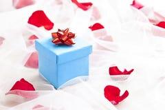 Blåttgåvan boxas med den röda pilbågen på bröllop skyler Royaltyfri Foto