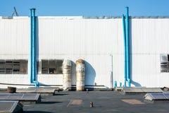 Blåttrör på den industriella väggen royaltyfri bild