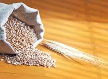 Blé et oreilles renversés de blé sur un fond en bois Photo stock