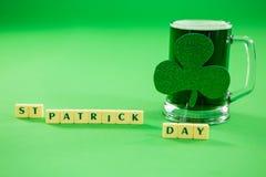 Blöcke St. Patricks Tagesmit Becher des grünen Bieres und des Shamrocks Stockbild