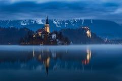 Blödd sjö och slott med vattenreflexion på gryning med lynnig molnig himmel, Slovenien, Europa royaltyfri fotografi