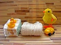 Blöjaleksaken ställer in för barn och att stapla blöjor på en bambubakgrund med en gul andleksak royaltyfri fotografi