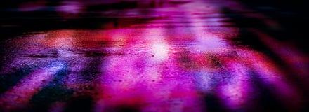 Blöta asfalt efter regn, reflexion av neonljus i pölar Ljusen av natten, neonstad abstrakt bakgrundsdark royaltyfri foto