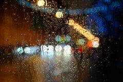 Blöta bilfönstret med bakgrunden av nattstaden Royaltyfria Bilder