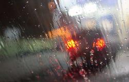 Blöta fönstret med bakgrund av sikten för nattstadstrafik Fotografering för Bildbyråer