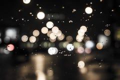Blöta fönstret med bakgrunden av sikten för nattstadstrafik Arkivbilder