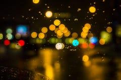 Blöta fönstret med bakgrunden av sikten för nattstadstrafik Royaltyfria Foton