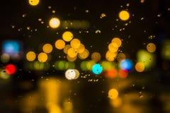 Blöta fönstret med bakgrunden av sikten för nattstadstrafik Royaltyfri Fotografi