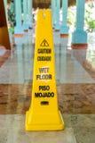 Blöta golvet och varna varning undertecknar in spanjor och engelska Fotografering för Bildbyråer