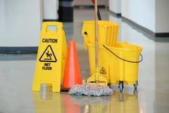 Blöta golvtecknet med golvmopp fotografering för bildbyråer