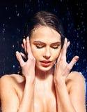 Blöta kvinnan vänder mot med bevattnar tappar. Fotografering för Bildbyråer