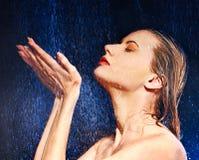 Blöta kvinnan vänder mot med bevattnar tappar. Royaltyfri Bild