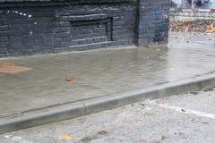 Blöta tegelplattor av en stadstrottoar i regnet royaltyfri foto