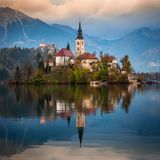 Blött Slovenien - härlig höstsoluppgång på sjön som blödas med den berömda pilgrimsfärdkyrkan av antagandet av Maria arkivbilder