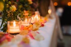 Blühen Sie Blumenblatt nahe Kerzen auf dem Tisch an der Hochzeitsdekoration Lizenzfreie Stockbilder