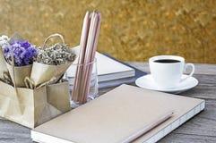 Blühen Sie Blumenstrauß mit Notizbuch die LatteKaffeetasse und die Gläser an Stockfotos
