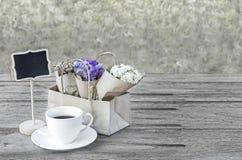 Blühen Sie Blumenstrauß und Kaffeetasse auf Holztischhintergrund für Mittwoch Lizenzfreies Stockfoto