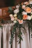 Blühen Sie Blumenstrauß von Rosen, von Pfingstrosen und von Eukalyptus auf einer festlichen Hochzeitstafel Stockfoto